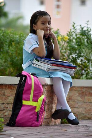 Studentessa triste bambino che indossa l'uniforme scolastica con i taccuini