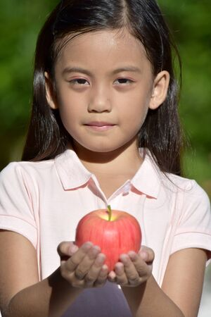 Serious Filipina Person With An Apple Imagens
