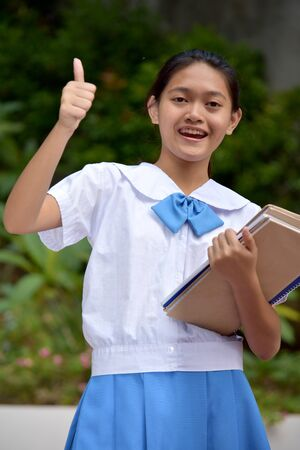 Youthful Minority Girl Student With Thumbs Up With School Books
