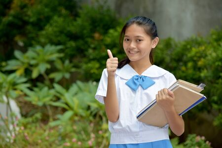 Beautiful Asian Female Student With Thumbs Up With School Books