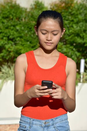 Unemotional Youthful Asian Female With Phone