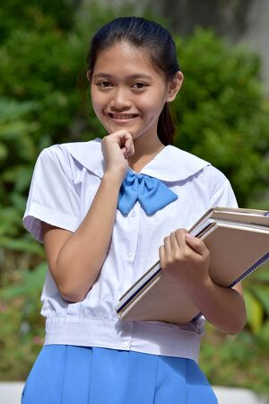 Youthful Filipina Female Student Making A Decision With School Books