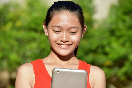 Smiling Cute Asian Girl With Tablet Imagens