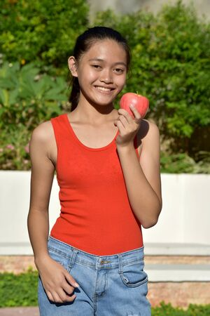 Smiling Filipina Teenage Female With An Apple