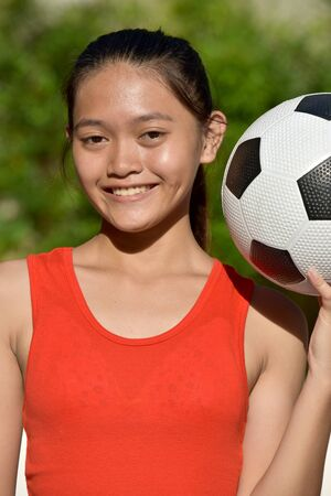 Smiling Fitness Asian Teen Athlete Female Soccer Player With Soccer Ball