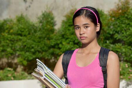 Depressed Filipina Female Student With Textbooks Stock Photo