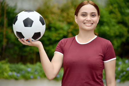 Smiling Athletic Asian Female With A Ball At Park