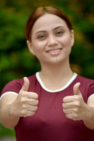 Youthful Filipina Female With Thumbs Up Wearing Tshirt