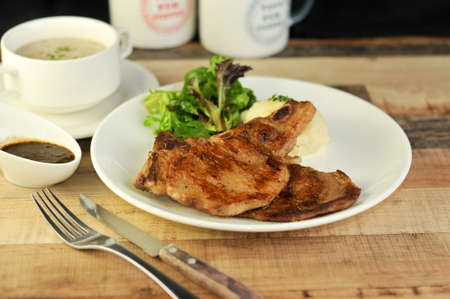 Close up of pork chop on wooden table