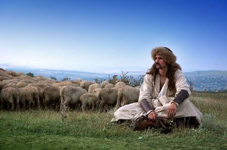 lonely shepherd with sheep outside Stock Photo