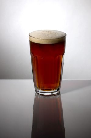 drunks: Backlit glass of home-made beer on reflective surface Stock Photo