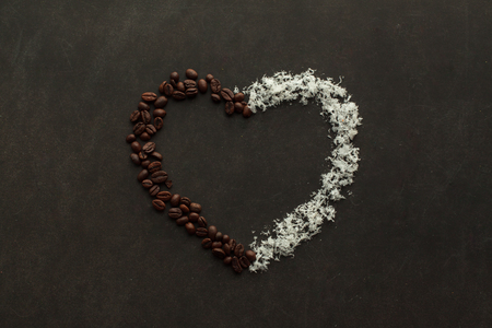 caffeine free: Heart made of coffee beans and coconut chips on the dark background with free space to write down.