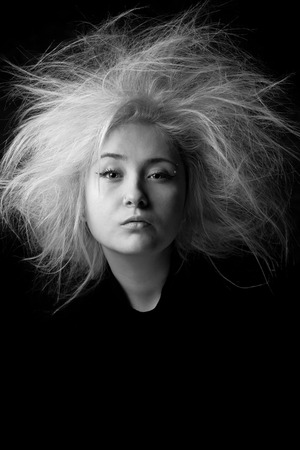 Portrait of an angry girl with a wild hair, photo in black and white. Tired woman with boring face.