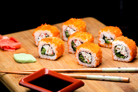 California Maki Sushi with Masago, roll made with Crab Meat, avocado and cucumber inside. Homemade japanese food with soy sauce. Menu for restaurant with asian meal.