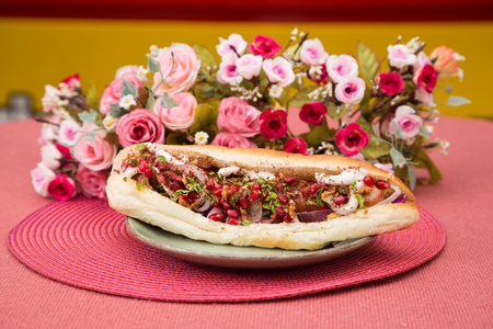 Delicious fast food lunch, when you got small time to eat. Unhealthy food for those, who always on hurry. Sandwich with french bun, colorful food with vegetables.