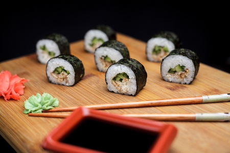 Sushi maki unagi hosomaki with eel, cucumber and unagi sauce. Homemade sushi with recipe on wooden cutting board.
