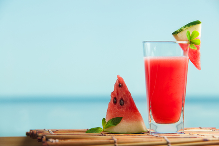 Fresh watermelon juice with mint, lemonade. Healthy drink for summer with vitamins, suits for vegetarian. Sea on the background.
