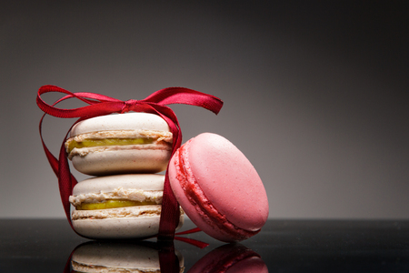 Delicious french dessert, macaroons, white and red, strawberry and white chocolate taste. Sweet snack as a romantic present for couples.