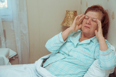 Elderly woman feeling sick in bed, holding her hands on a head. Headache in the morning. Standard-Bild