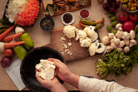 Preparing cauliflower for cooking, cutting vegetables on a cutting board. Healthy food for people on a diet.
