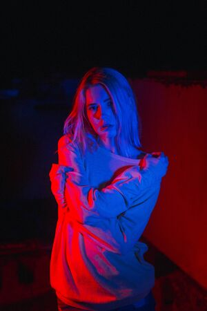 Blond woman into neon light. Nightclub life in the evening. Imagens