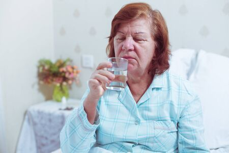 Aged woman drinking water after taking pill. Stockfoto