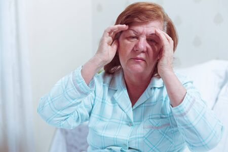 Senior woman sitting in bed at home with headache.