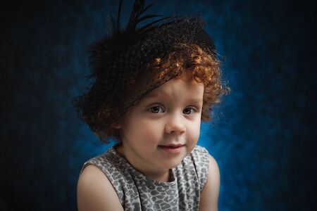 Little redhead funny girl in black hat. Stockfoto
