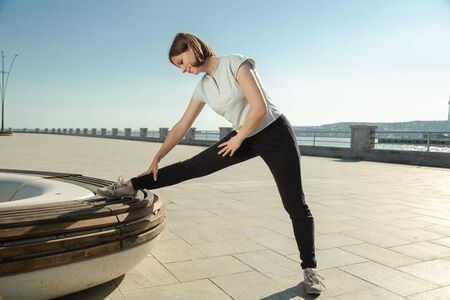 Young woman doing sport exercises outside with bench, concept of healthy lifestyle. Morning training before breakfast.