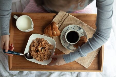 Breakfast in bed with coffee and corn flakes with milk. Serving tray in bed.