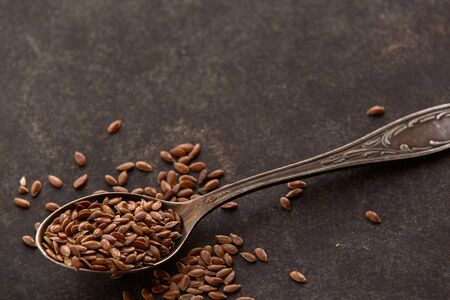Flax seeds into spoons on dark background. Ingredients for healthy lifestyle meal. Full of vitamins and minerals food.