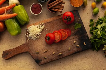 Sliced tomato on cutting board with knife. Cooking vegetarian food, vegetables ingredient for healthy eating.