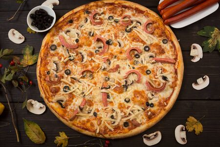 Italian traditional pizza with sausages and mushrooms and olive. Fast food for lunch.
