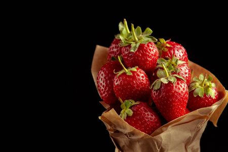 Ripe red strawberry on dark background as source of vitamins. Fresh organic vegetarian food.