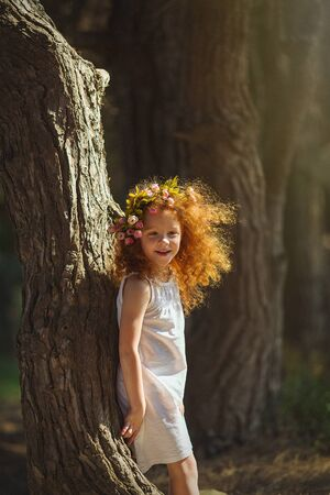 Red hair girl walking into woods with flowers.