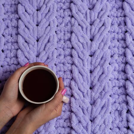 Cup of hot chocolate into woman arms on knitted plaid. Homemade knitted plaids for cosy time in winter at home.