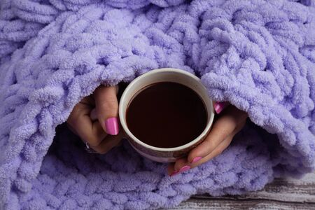 Cup of hot chocolate into woman arms on knitted plaid. Homemade knitted plaids for cosy time in winter at home. Foto de archivo - 137893705