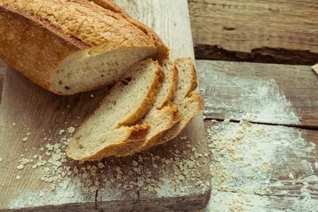 Sliced gluten free bread on wooden table. Healthy lifestyle with homemade organic bread. Foto de archivo - 137893748