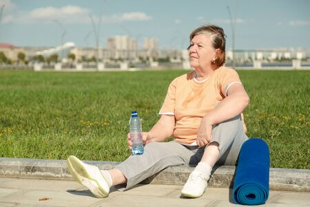 Pensioner woman resting after training in park.