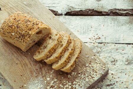 Sliced homemade gluten free bread on cutting board. Foto de archivo - 137893724