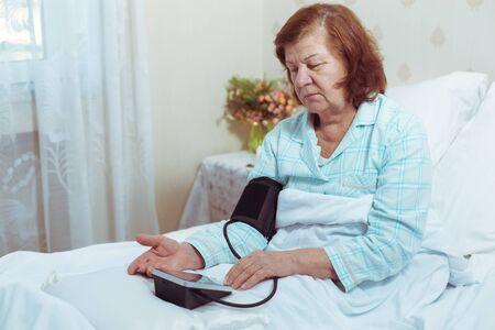 Femme âgée vérifiant sa tension artérielle assise dans son lit.