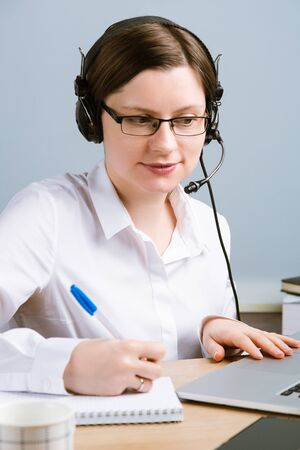 Woman with headset working in office to solve problems. Call center operator working from home. Фото со стока