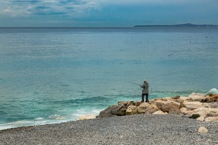 Cote d'Azur coast line with lonely fisherman trying to catch some fish. Tranquin photo with hobby concept. Pensioner activity after retirement.