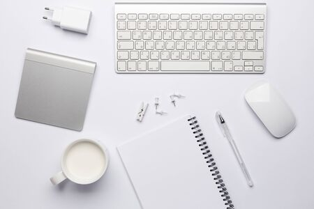 Empty white notebook with pen, working place with keyboard and touchpad. Free white space for notes and text. Foto de archivo