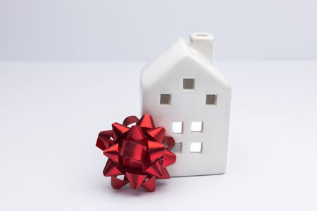 Buying house concept, investment in property. White home with red bow. Insurance for new property.