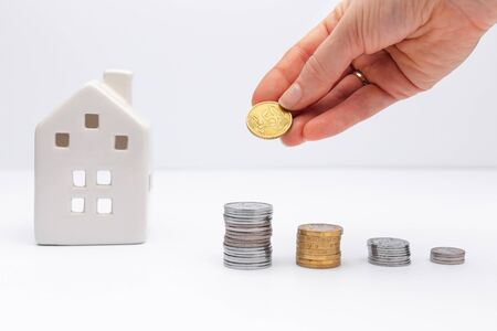 Concept of investment in property, hand putting coin with white house on background. Taking loan in bank to buy house.