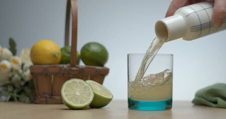 Just squeezed fresh lime juice pouring in glass to have breakfast. Healthy lifestyle with organic food.