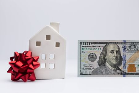 White house with coins as a concept of investment in property. Take loan in bank to buy house.