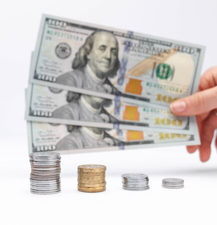 Concept of investment, hand holding dollar cash money with coins. Taking loan in bank to buy house.