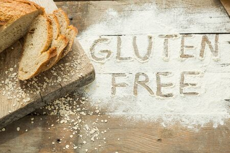 Gluten free word written on a flour with homemade bread. Concept of special diet for people with allergy. High quality photo Stok Fotoğraf